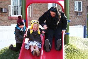 A Children's Center teacher and student play on a slide.
