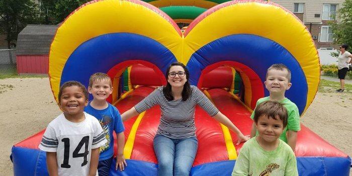 Children's Center teacher aide and children on bounce house